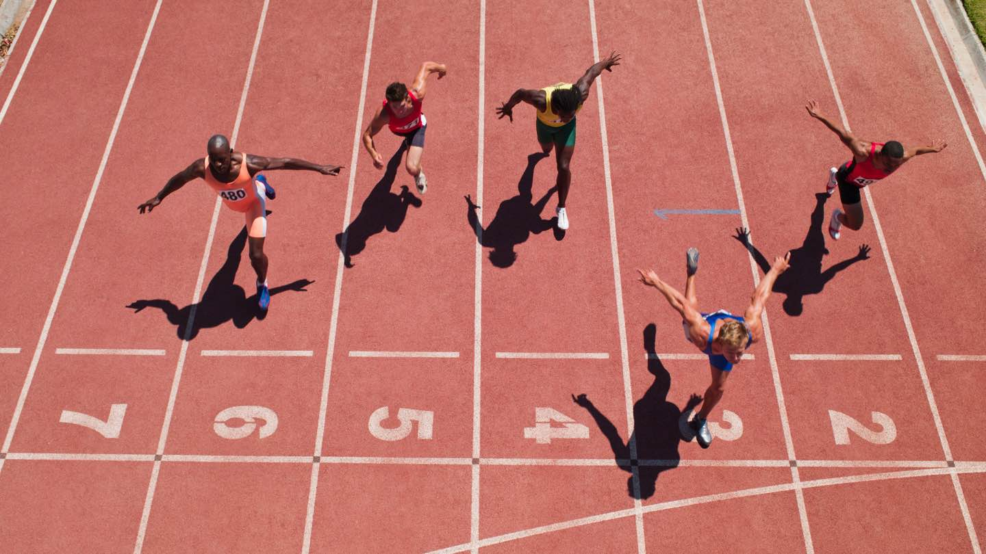 Aerial view of five runners crossing a finish line.