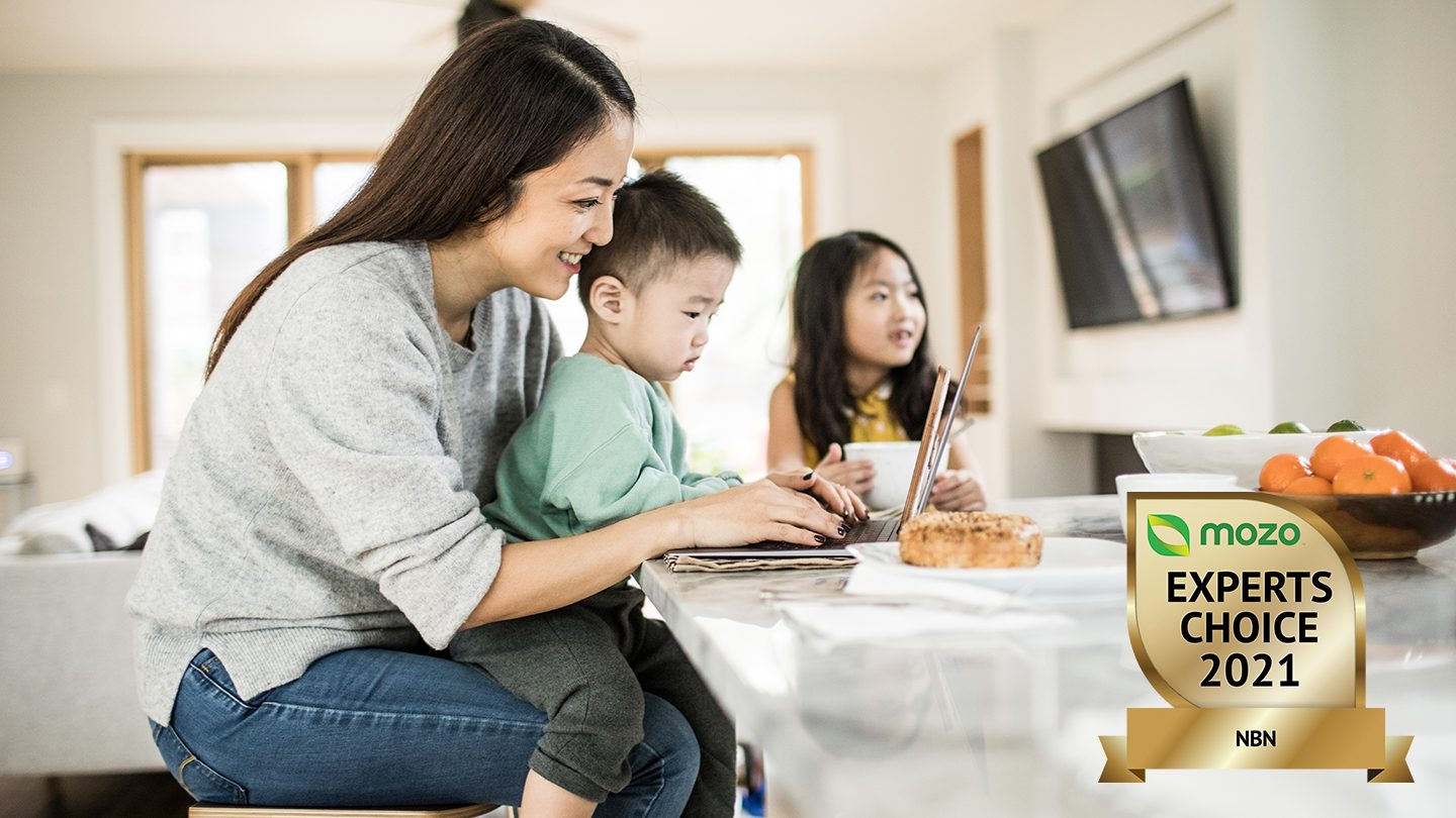 A mother sits at kitchen counter with a laptop and two children.