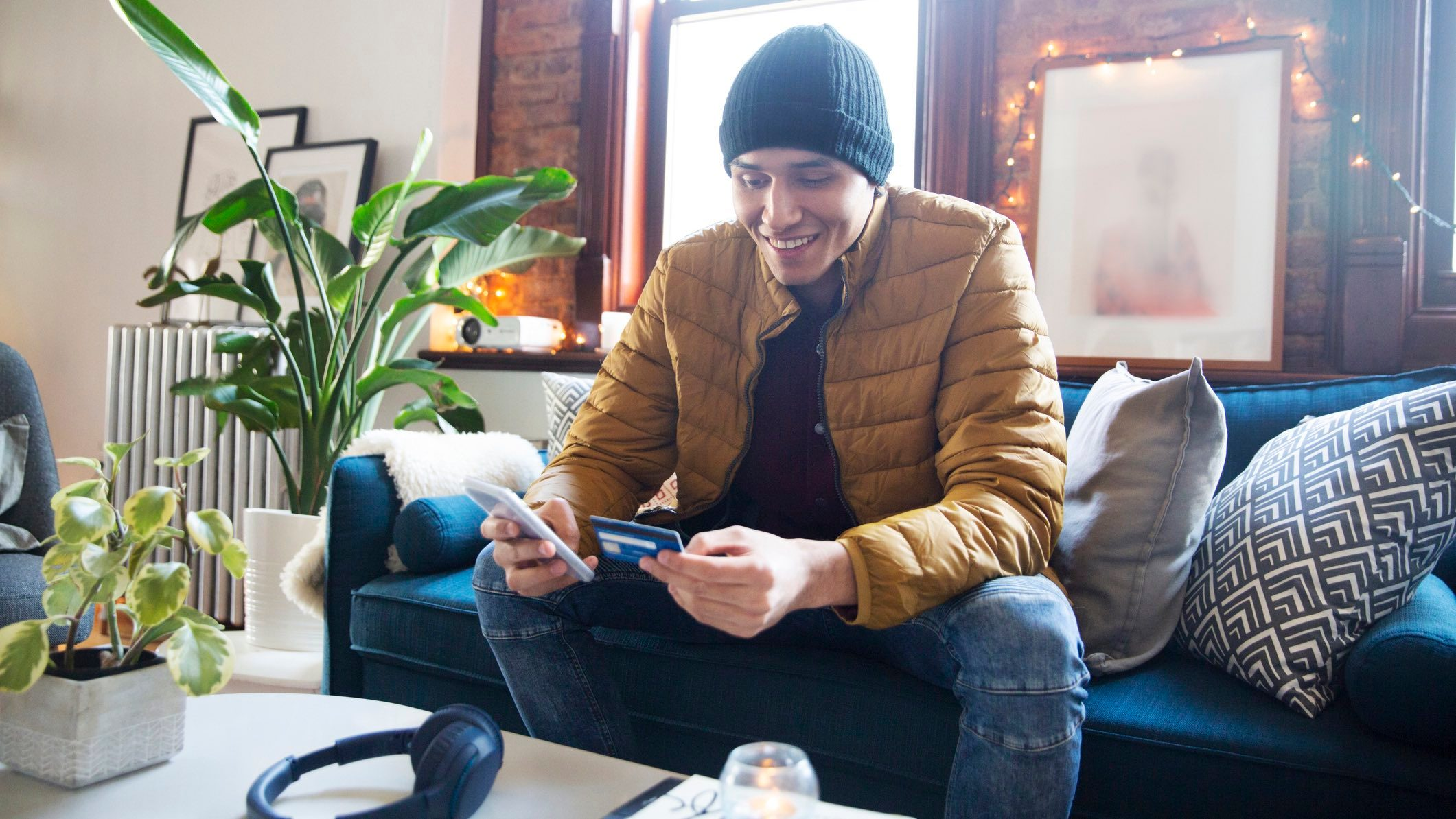 Man in a beanie and coat sitting on a lounge, using his phone and credit card to make EOFY purchases.