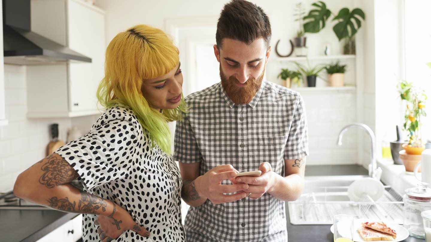 Man and woman stand in kitchen looking at app on phone.