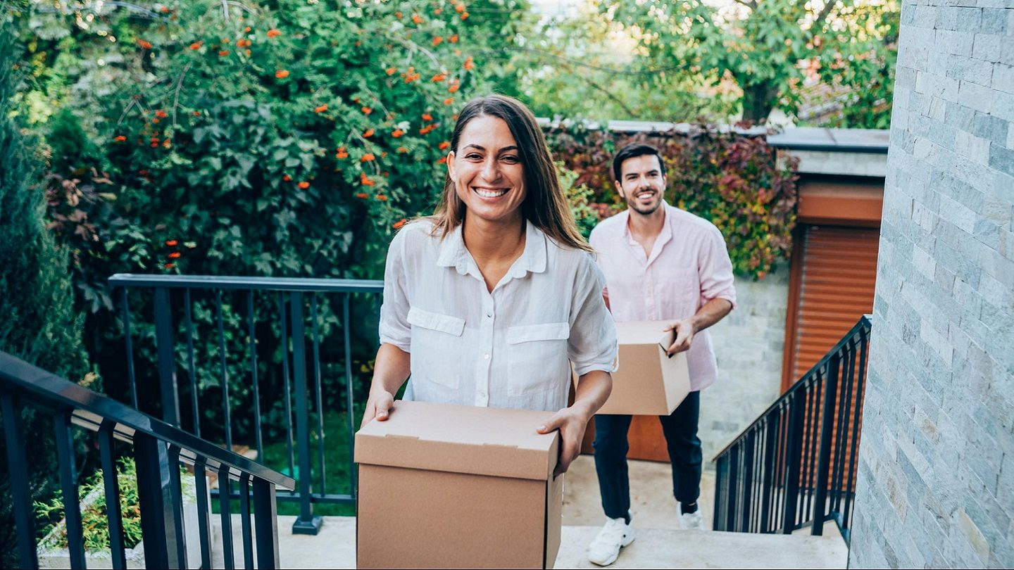 Couple moving boxes upstairs into new homes