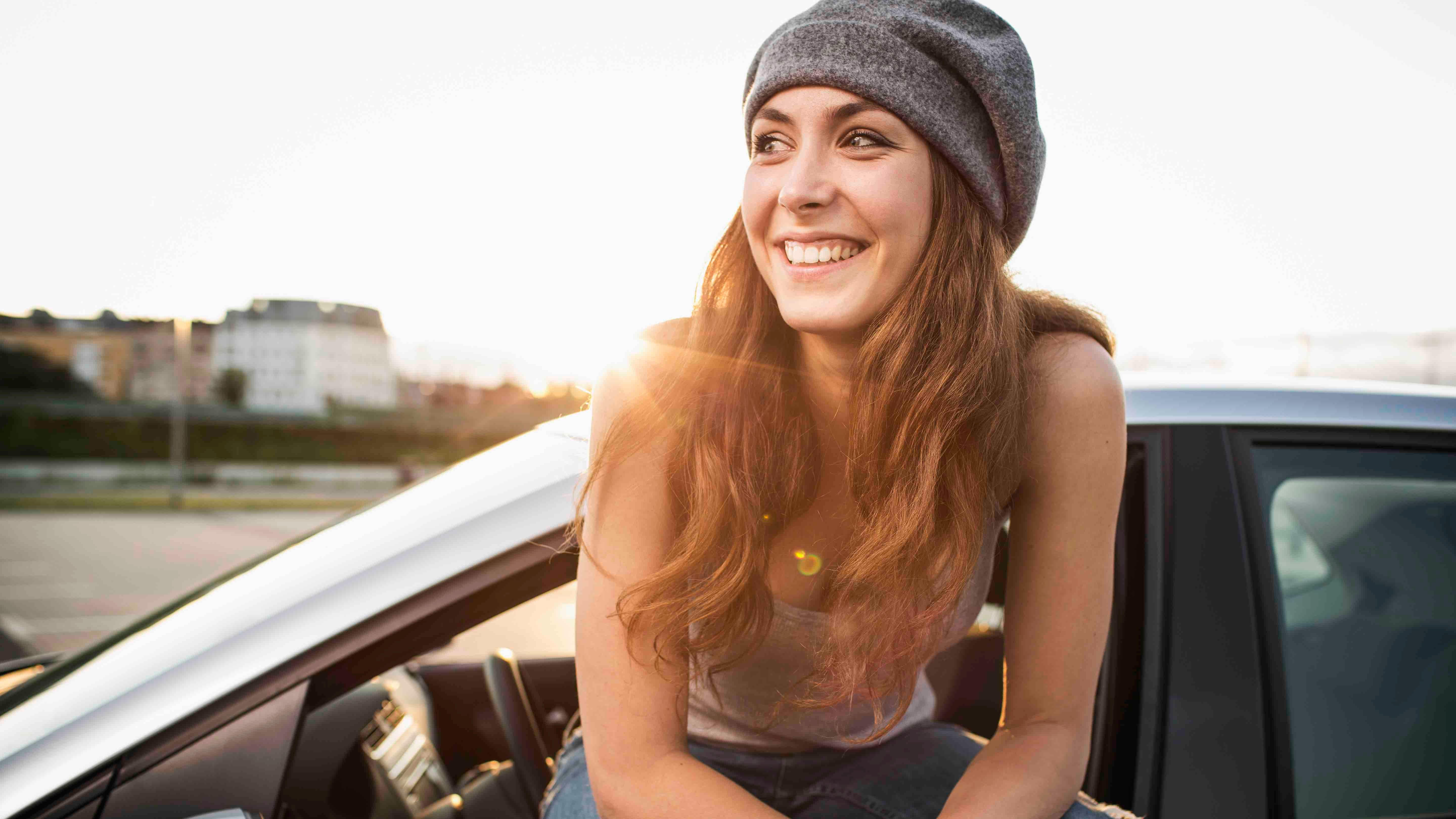 Woman with Poncho car insurance smiling as she sits on the window of her car thinking about sustainable transport.