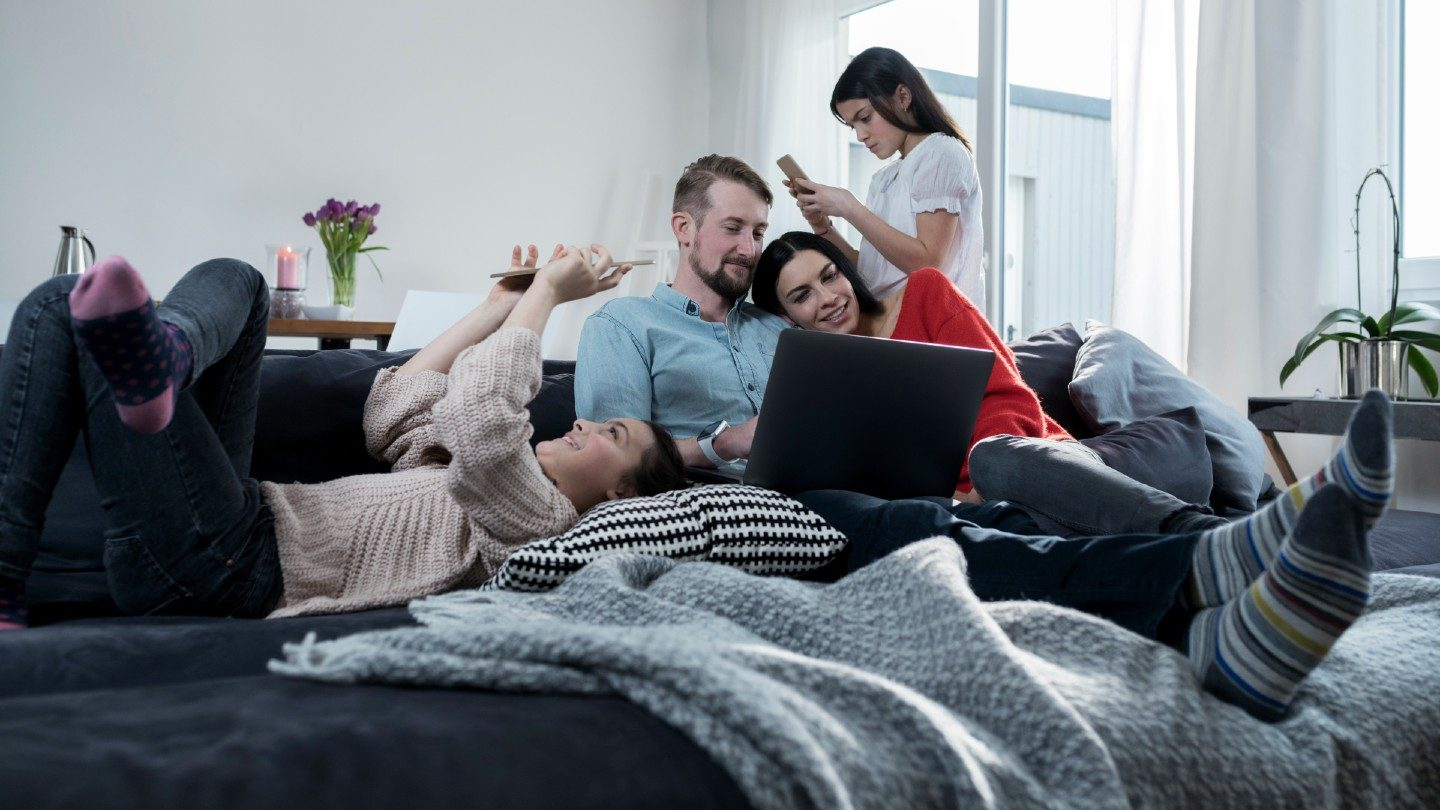 Family sitting on lounge using internet devices