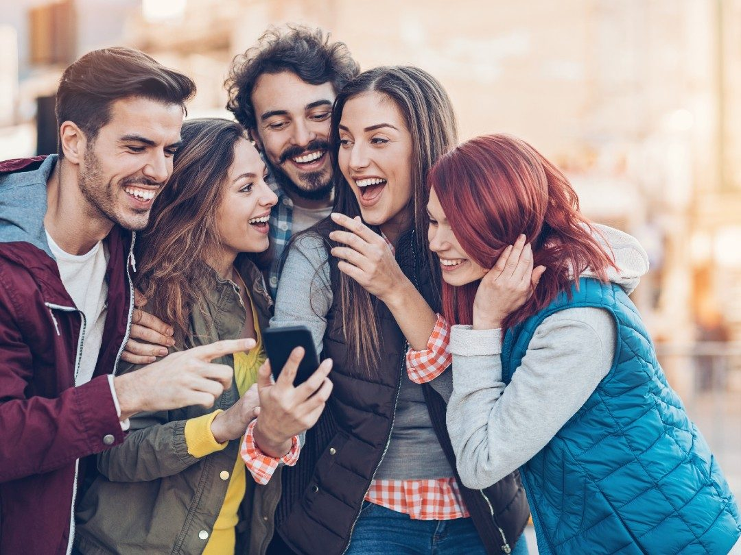 Friends happy smiling at phone internet