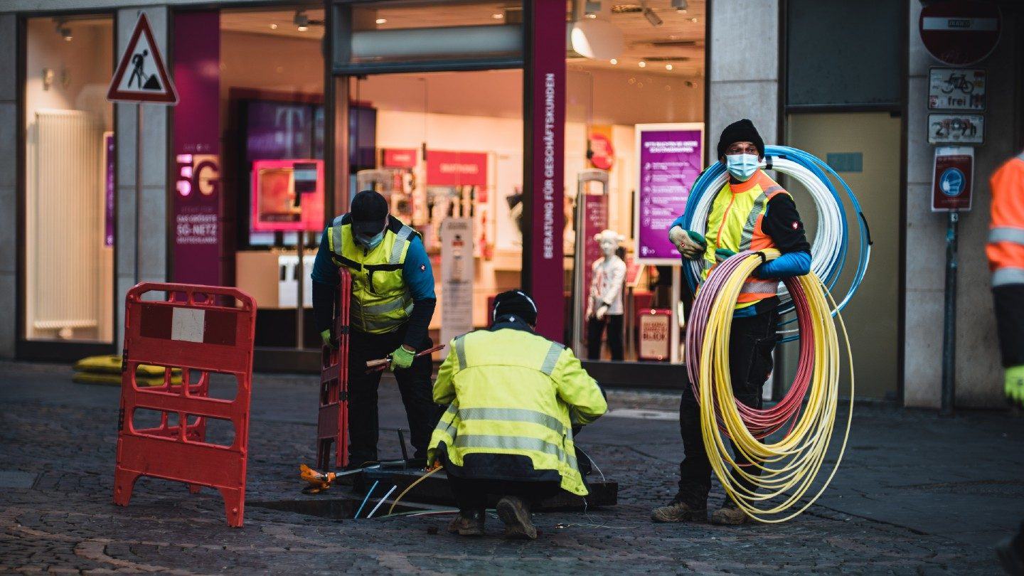 Technicians working on internet cable in a city