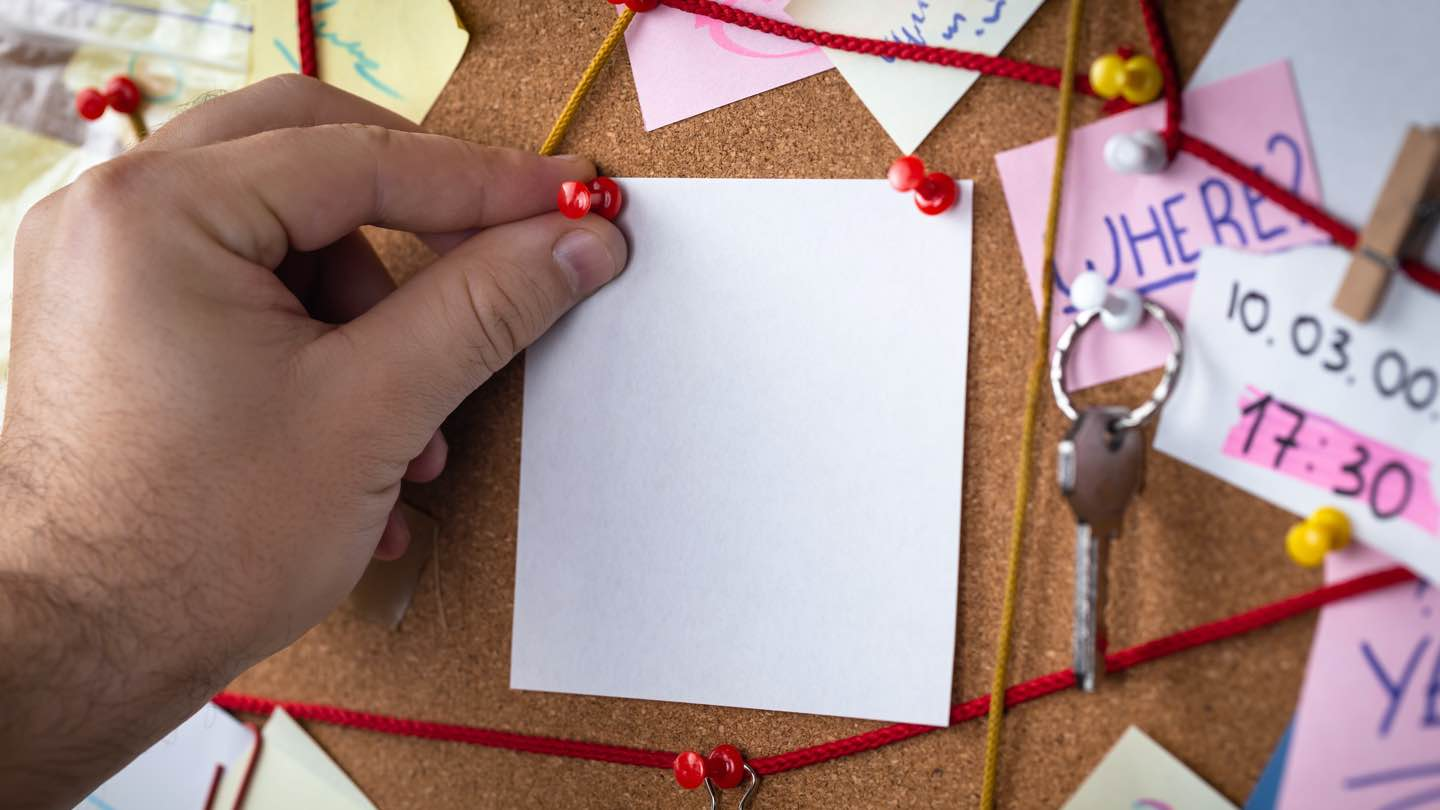 Hand pins paper to a detective board.
