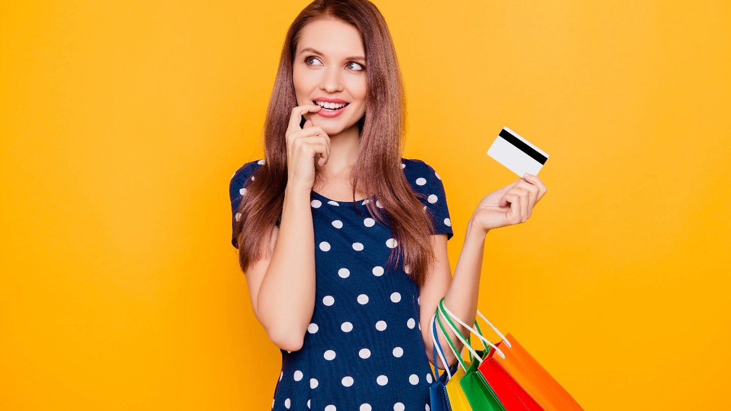 woman in polka dot dress holding credit card and shopping bags thinking about credit benefits