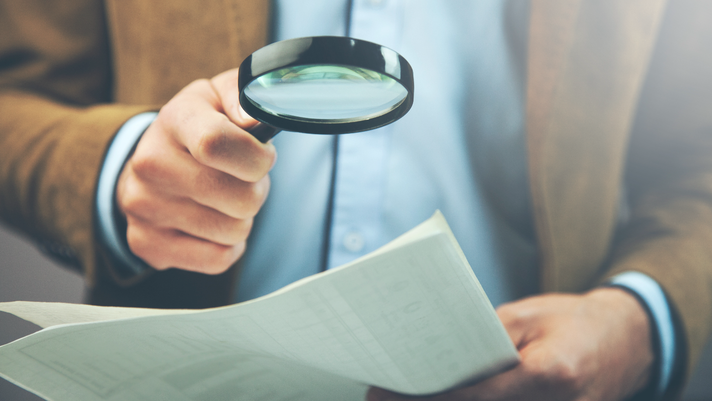 Man with magnifying glass investigating money transfer scams