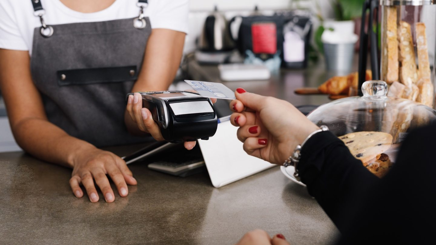 a close up of a woman tapping her low interest credit card at a credit card machine at a cafe