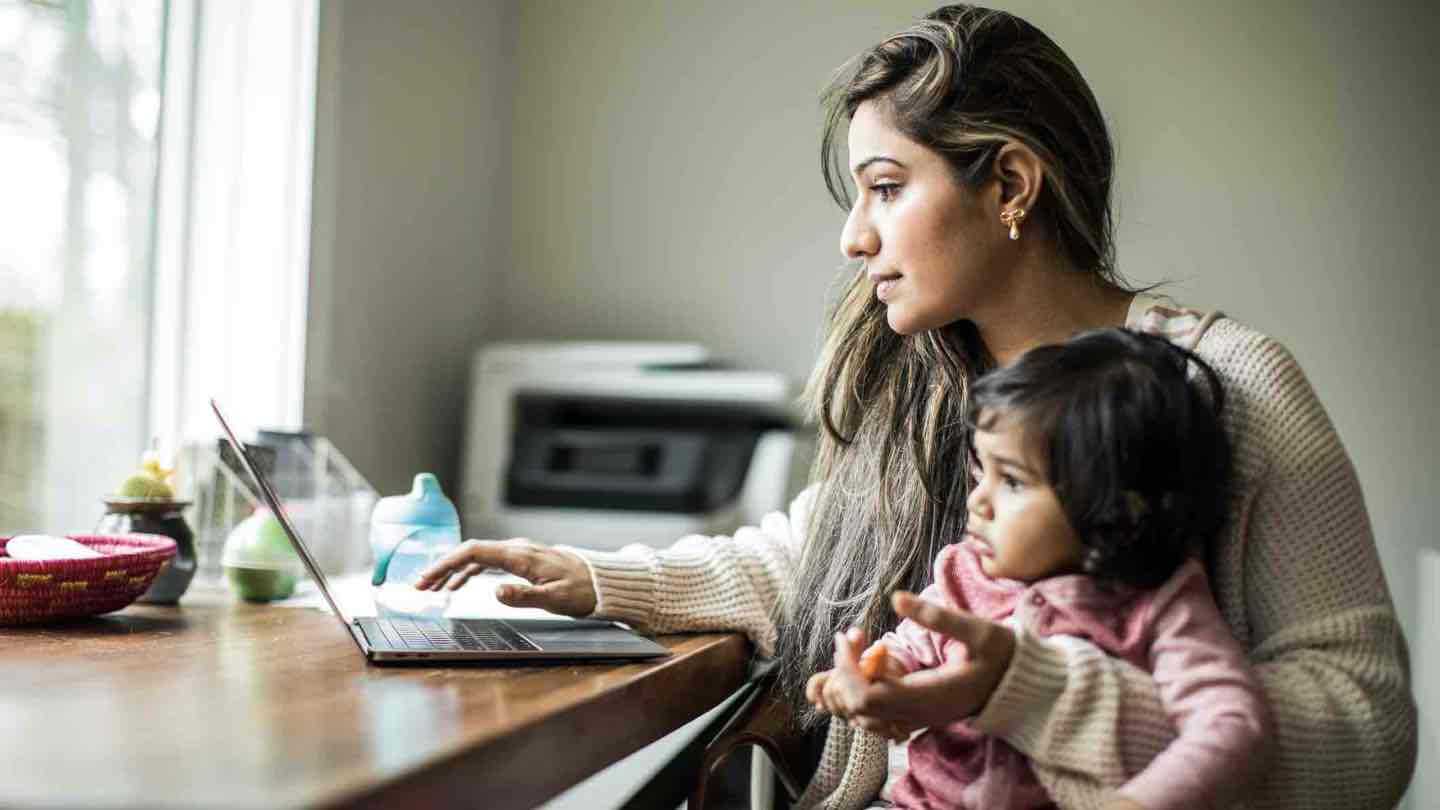 A woman sits at a table looking at a laptop with a child on her knee.