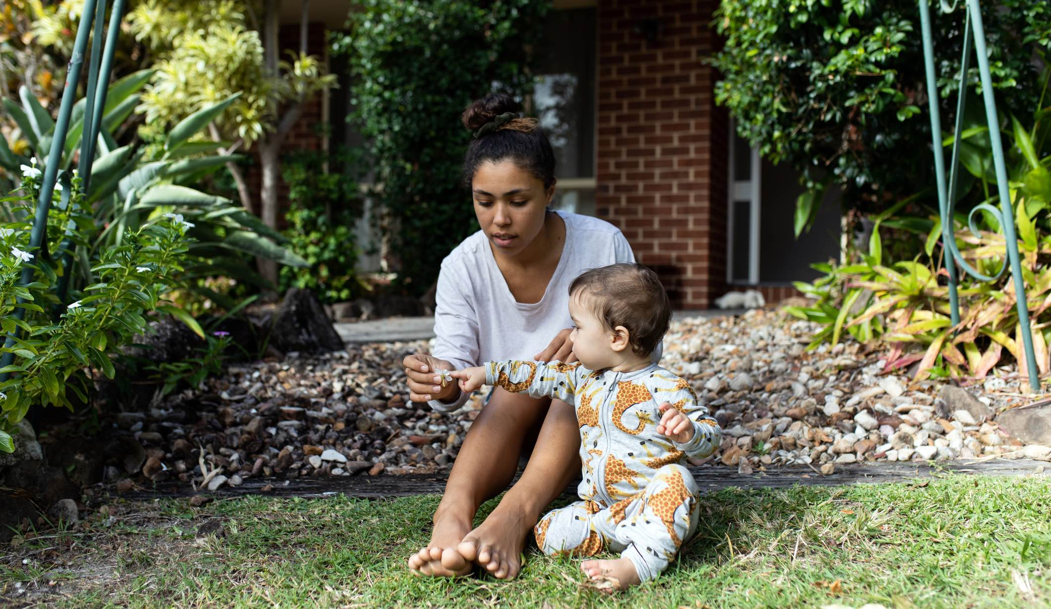 Woman and child sitting on lawn after home insurance claim.