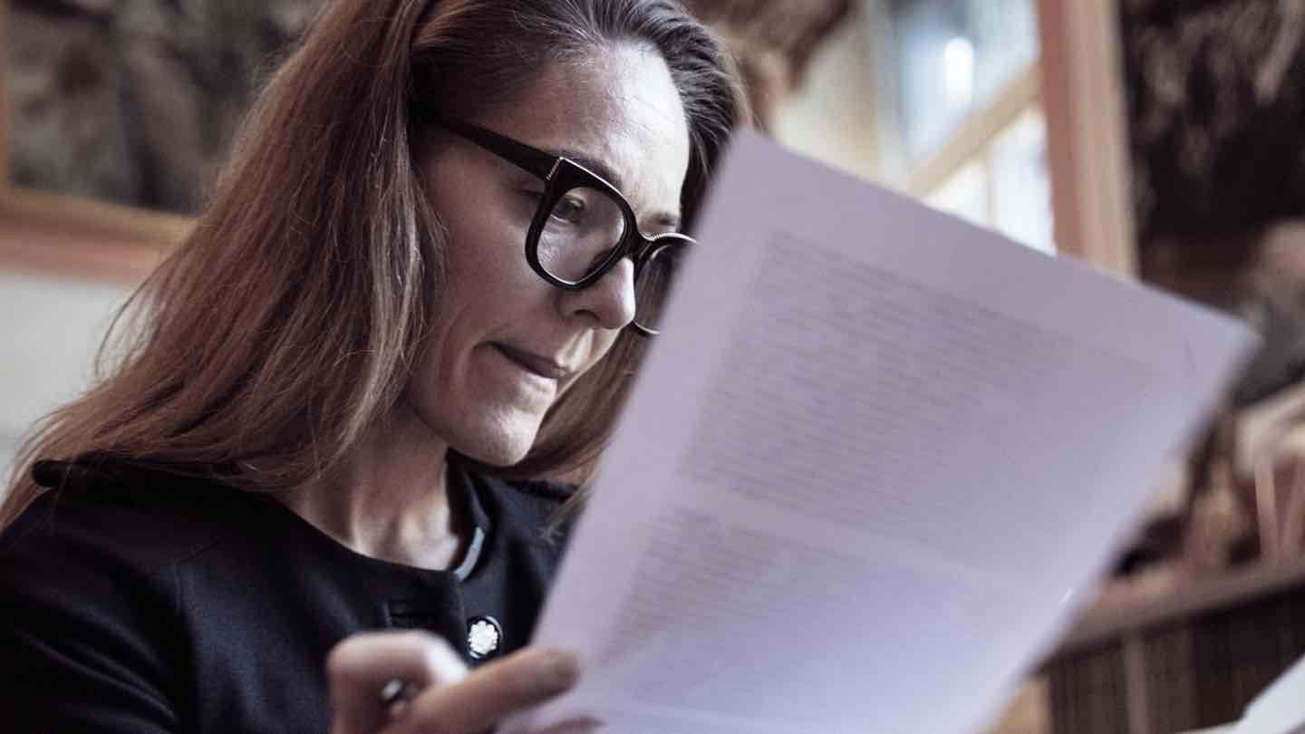 A woman sits reviewing paperwork.