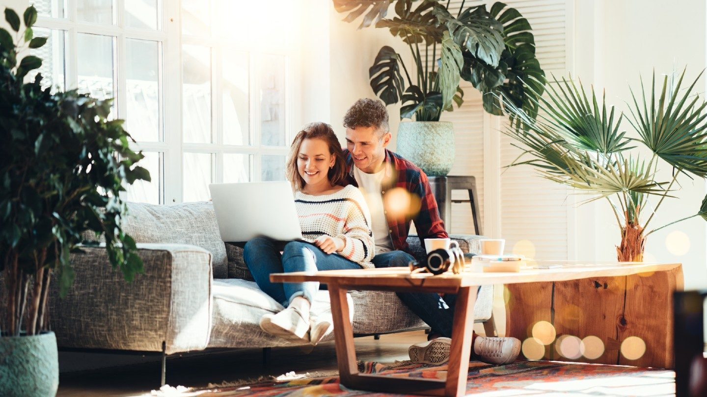 Couple on lounge smiling at laptop