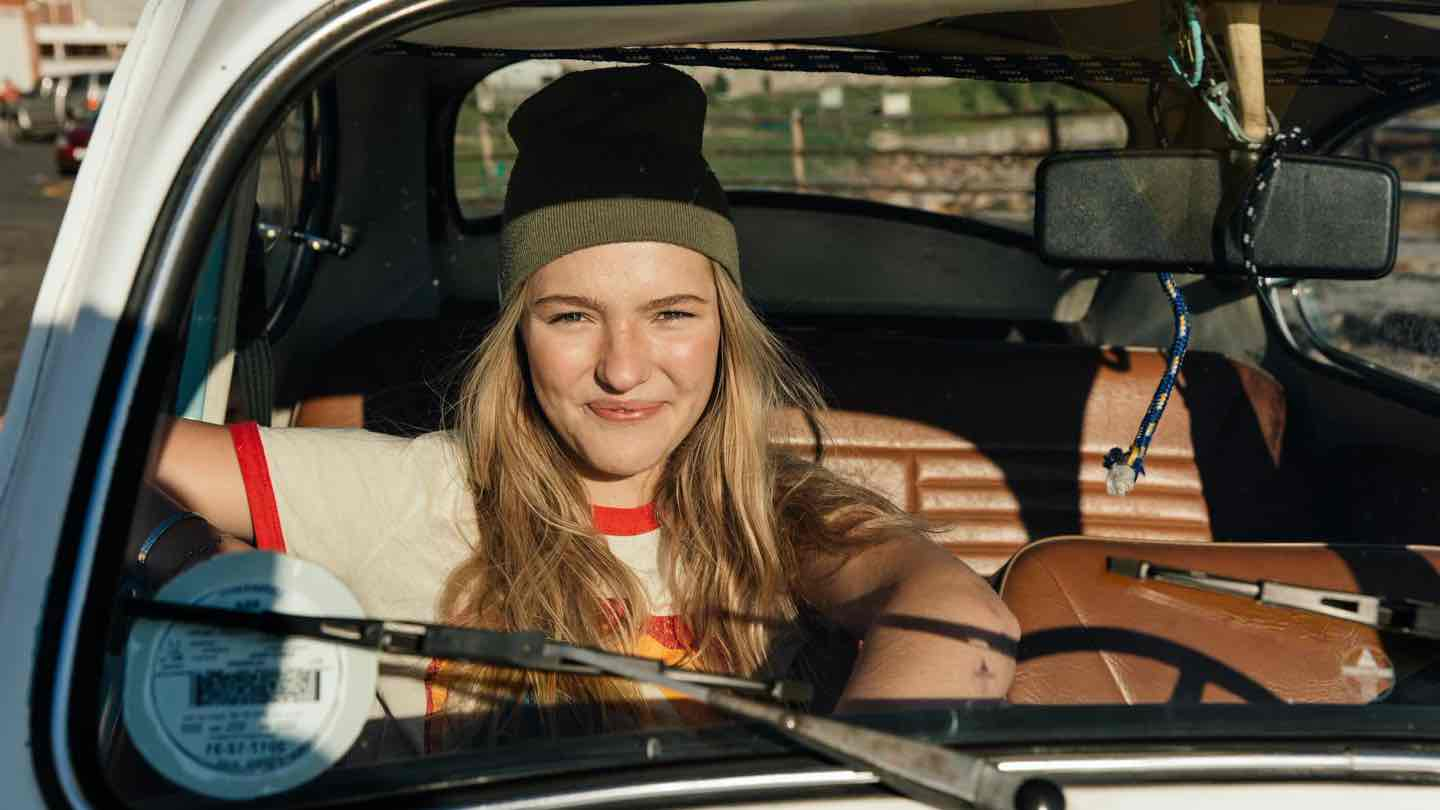 Woman with beanie on, sits in car driver's seat.