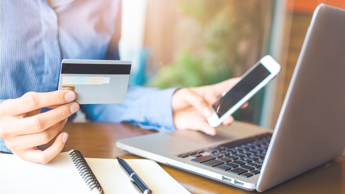 woman holding no annual fee rewards credit card while redeeming earning points while shopping online on her phone and laptop