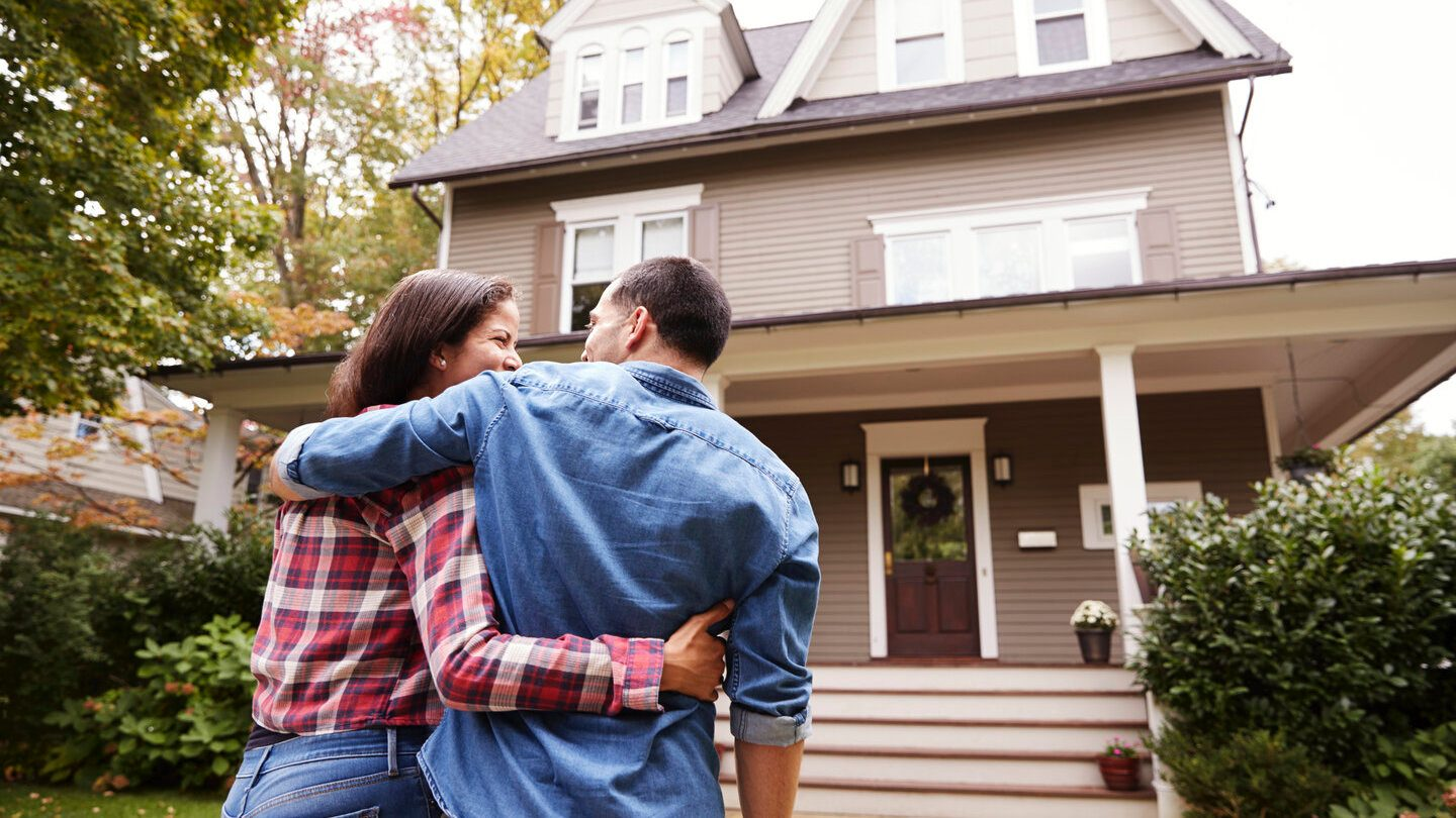 first time homeowners in front of their new home