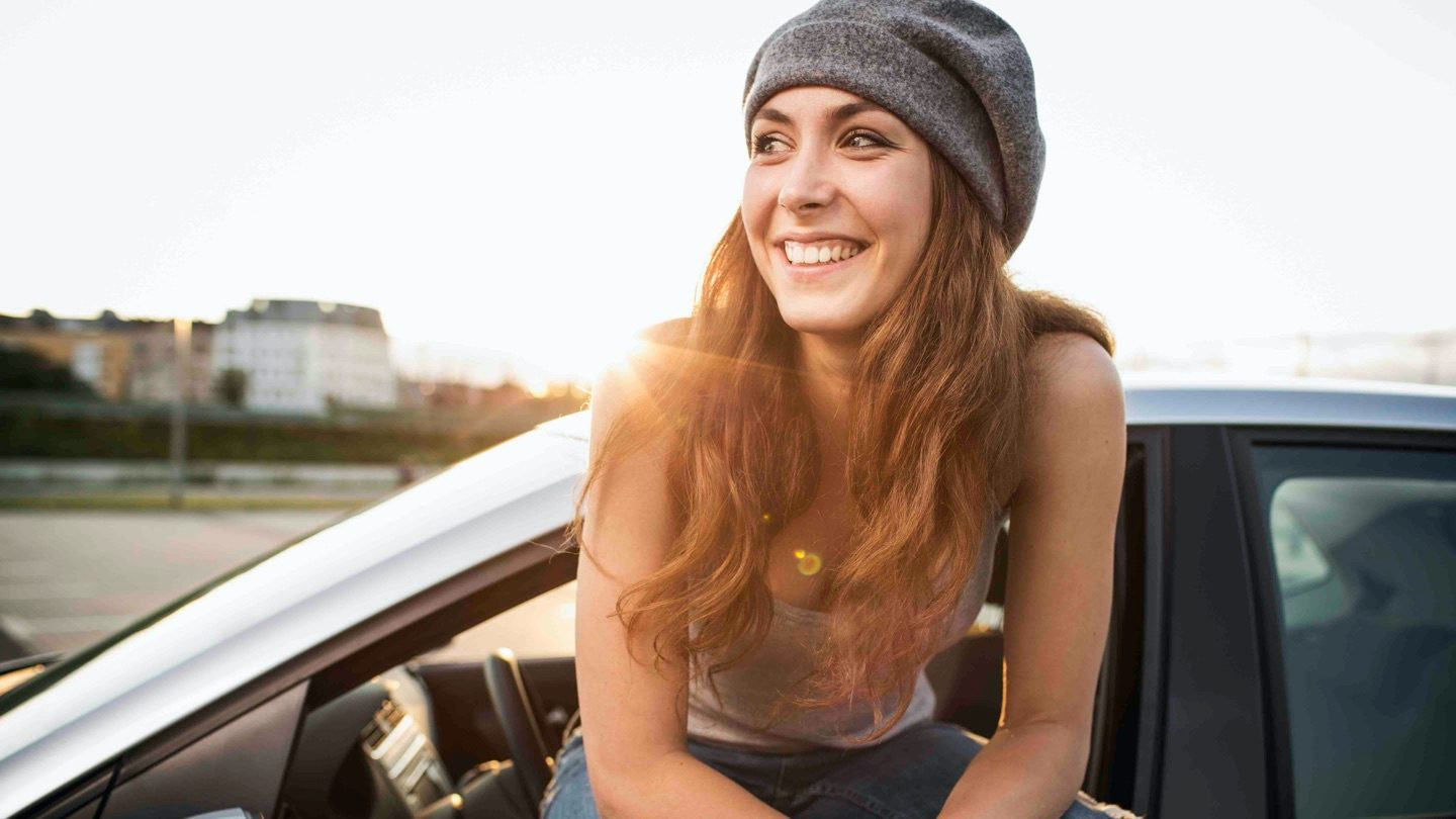 Woman sits in car, smiling.