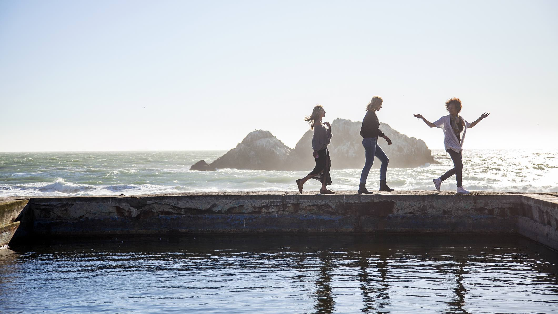 Three people walking on the edge of an ocean pool, discussion spending on travel in 2021.