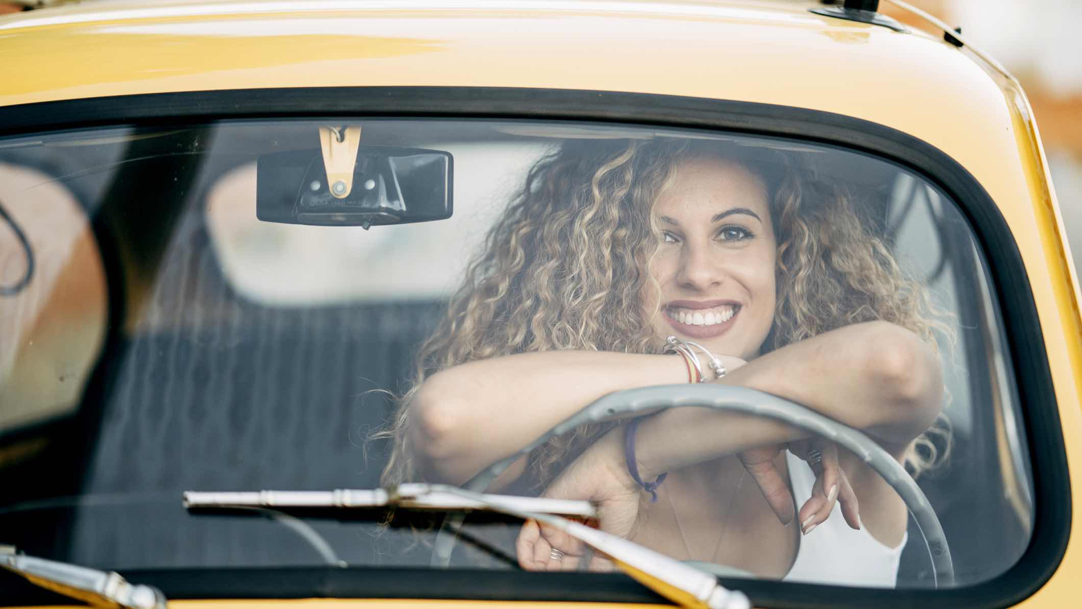 Woman sitting in car smiling after getting a car insurance refund.