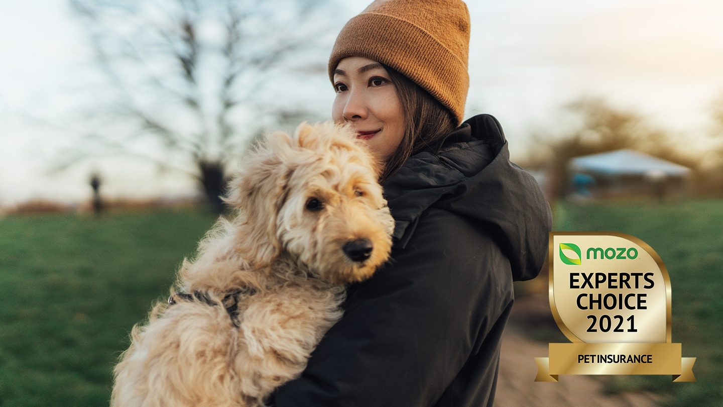 Woman stands holding fluffy dog.