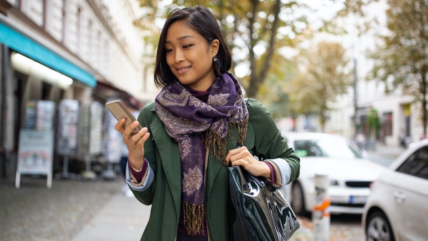 Woman stands in street holding smartphone and smiling.