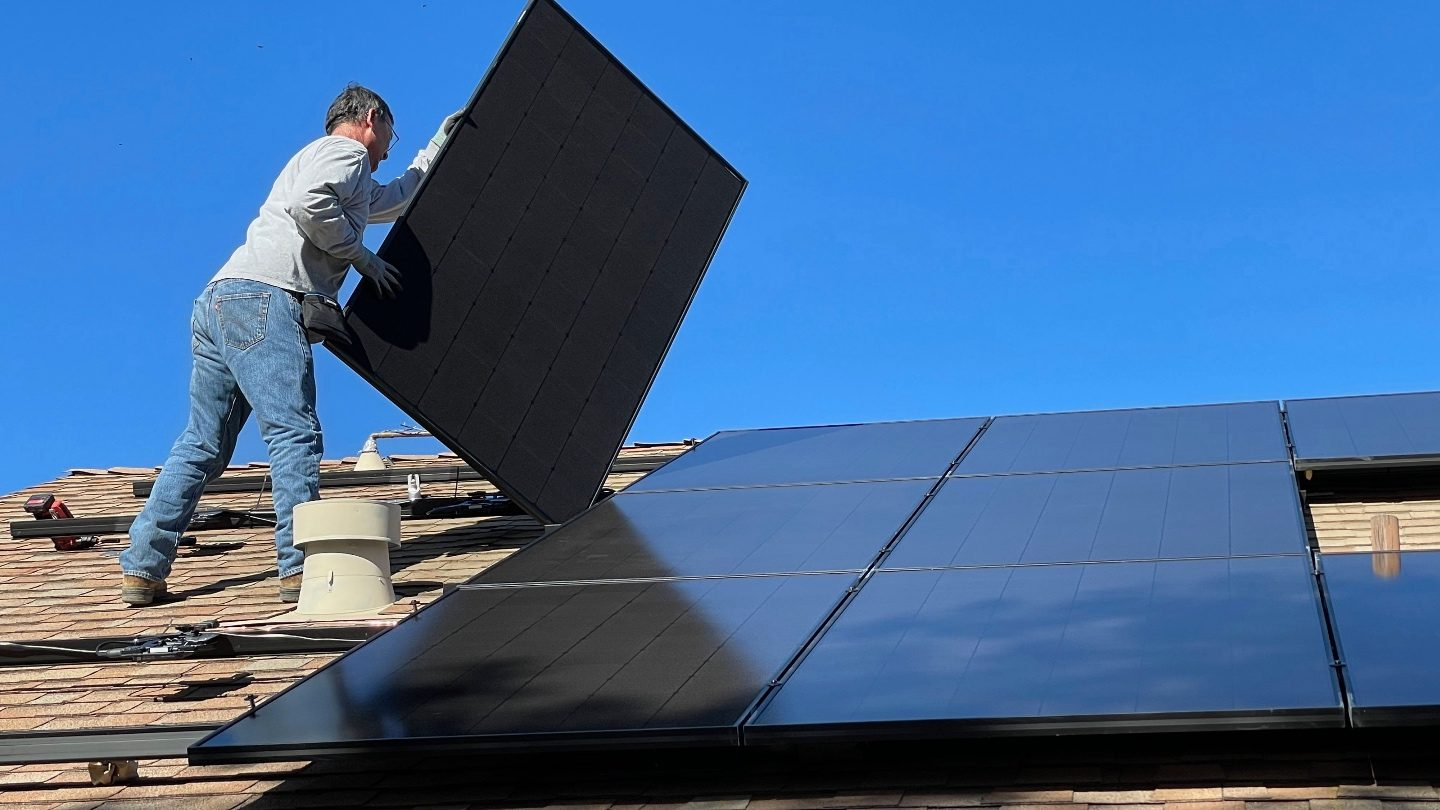 man in jeans standing on the roof of his house installing solar panels after getting a green personal loan