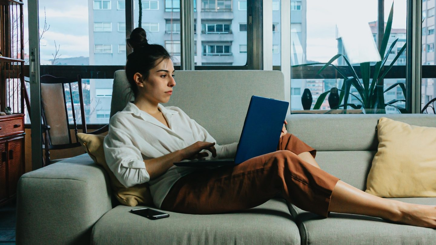 brunette woman in orange pants and a white blouse is sitting on her grey couch on her laptop, applying for a personal loan online during lockdown
