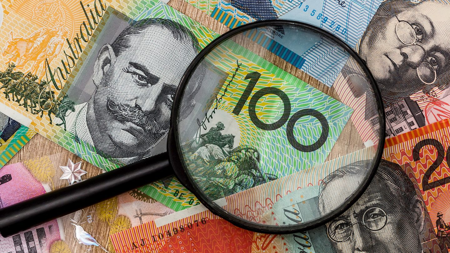 close up magnifying glass on australian money saved through good personal loan management