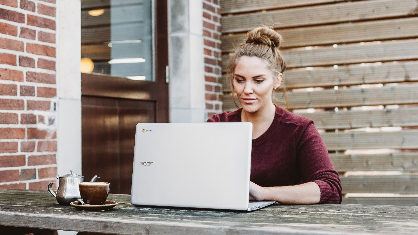 woman sitting outside at a wooden table with a black coffee on her laptop looking at personal loan rate cuts during covid
