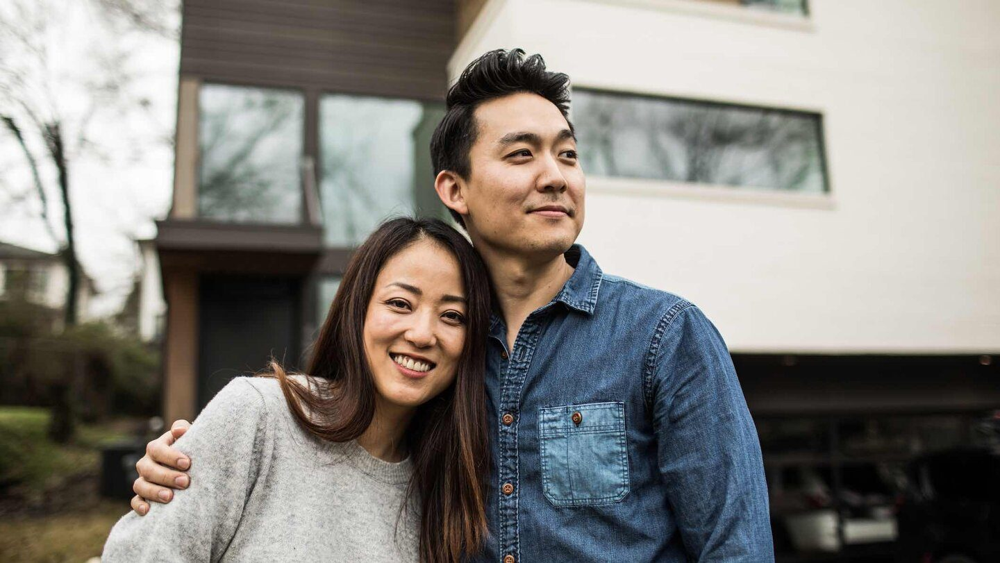 Couple in front of their home happy to have refinanced