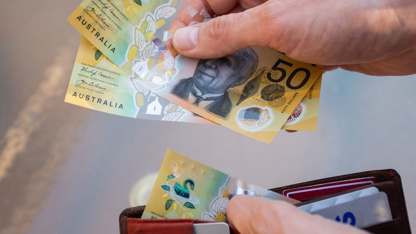 person-taking-50-dollar-australian-notes-from-wallet