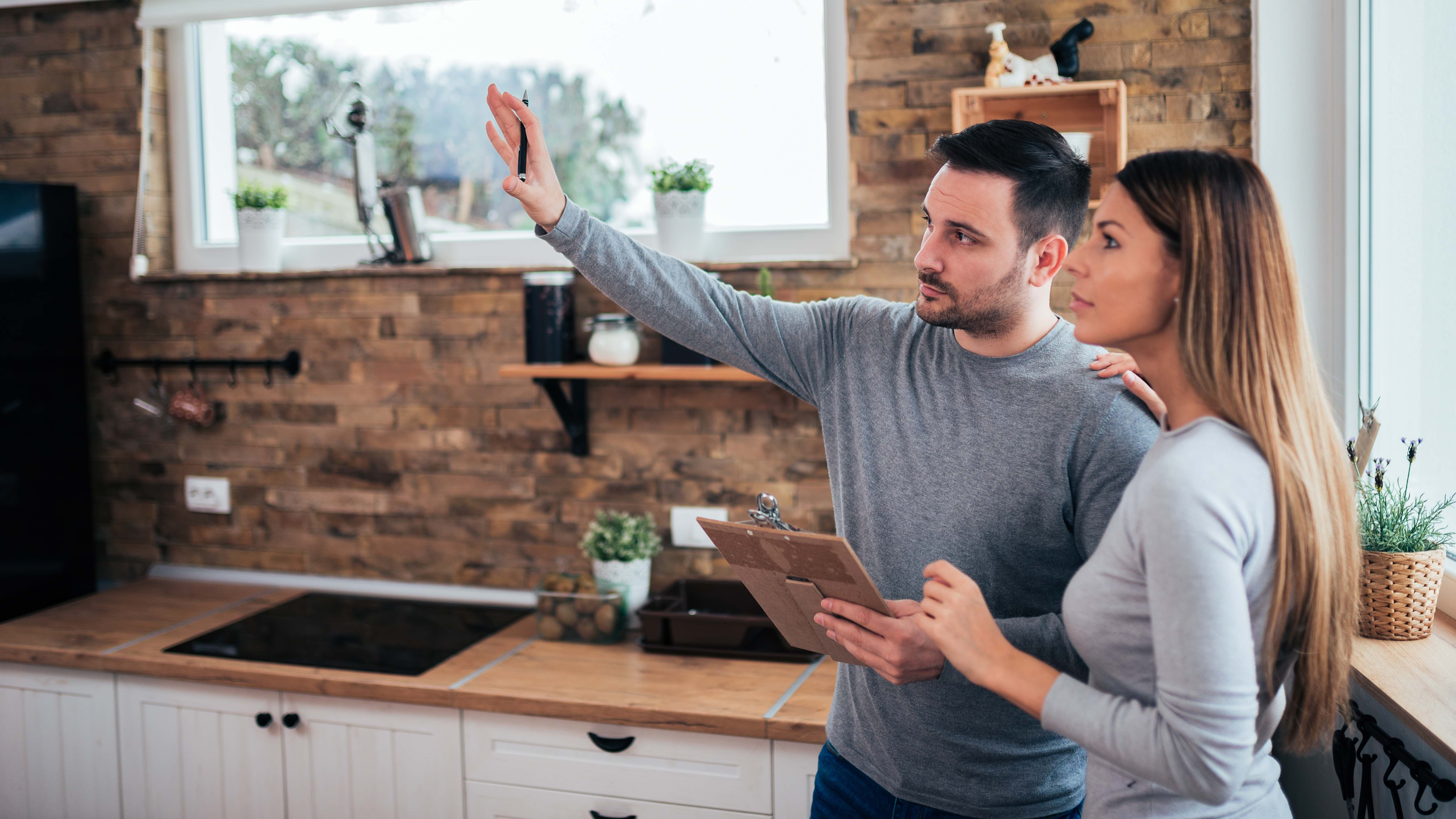 Couple standing in kitchen holding a clipboard, considering investment property purchase.