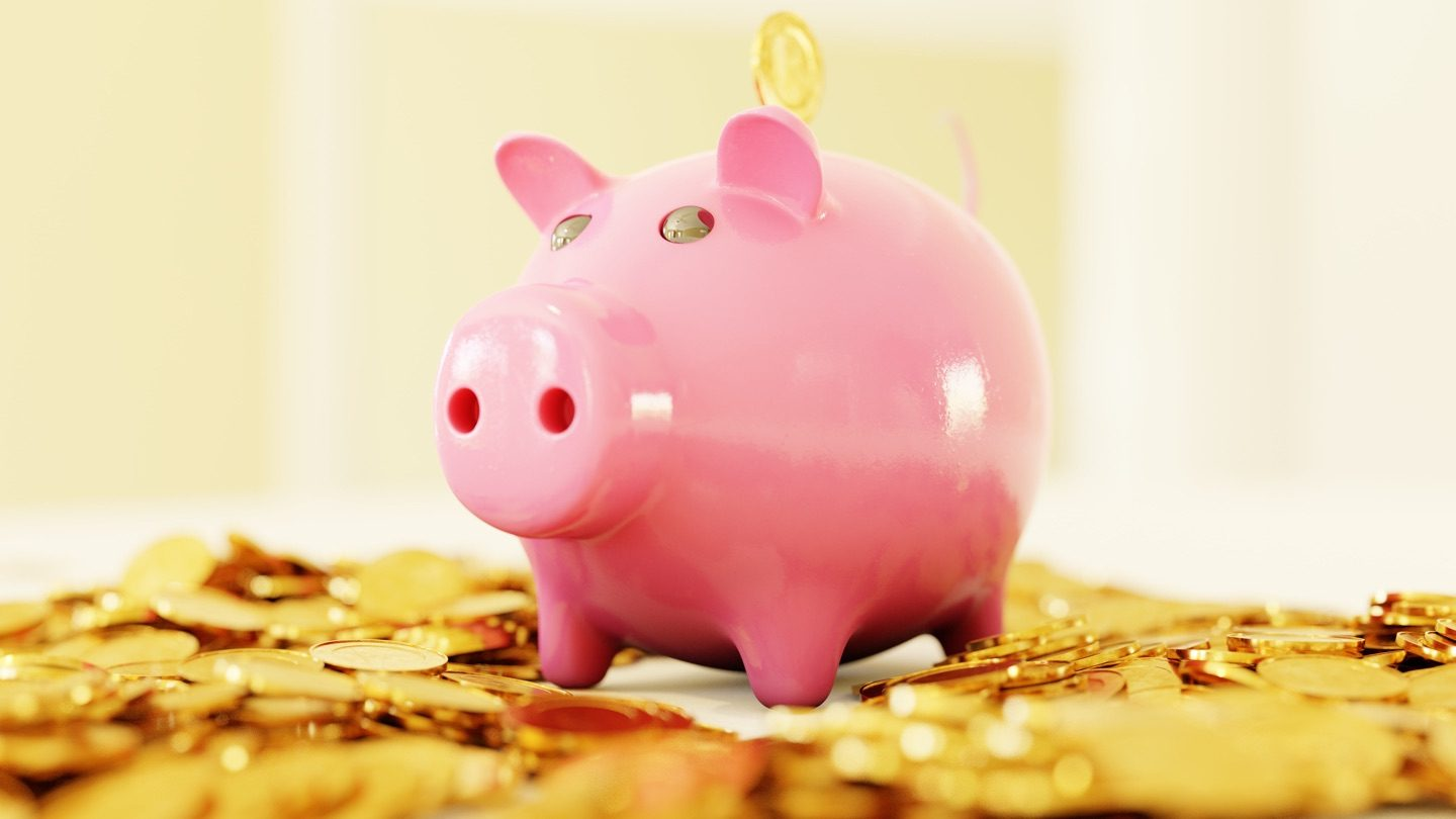 A pink piggy bank sits on a stash of gold coins.