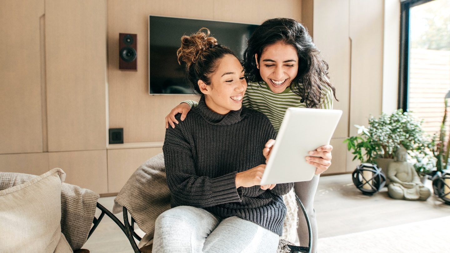 two girls sitting in living rooms looking at an ipad looking at good personal loan rates because they have excellent credit
