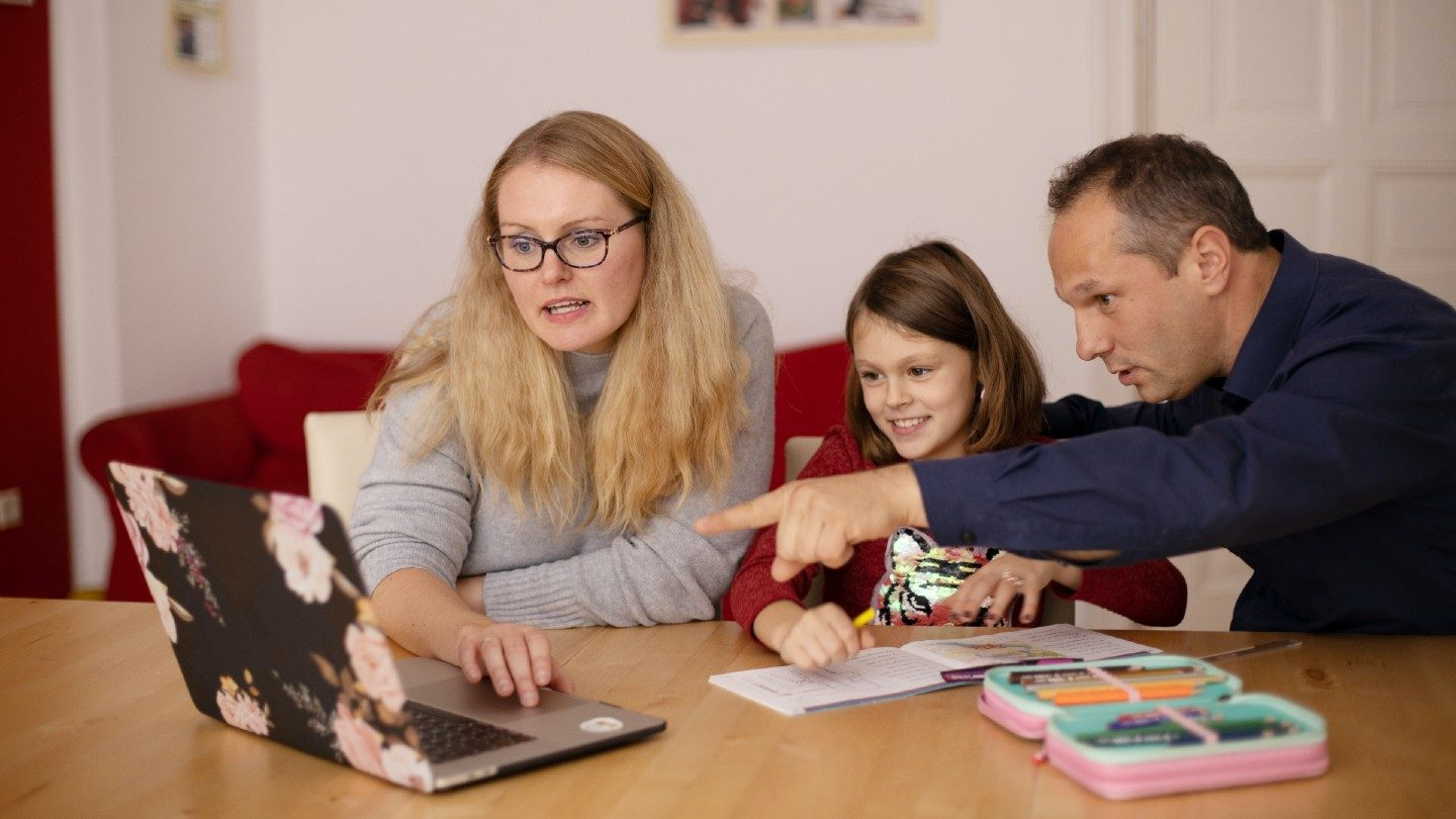 Family using laptop at table
