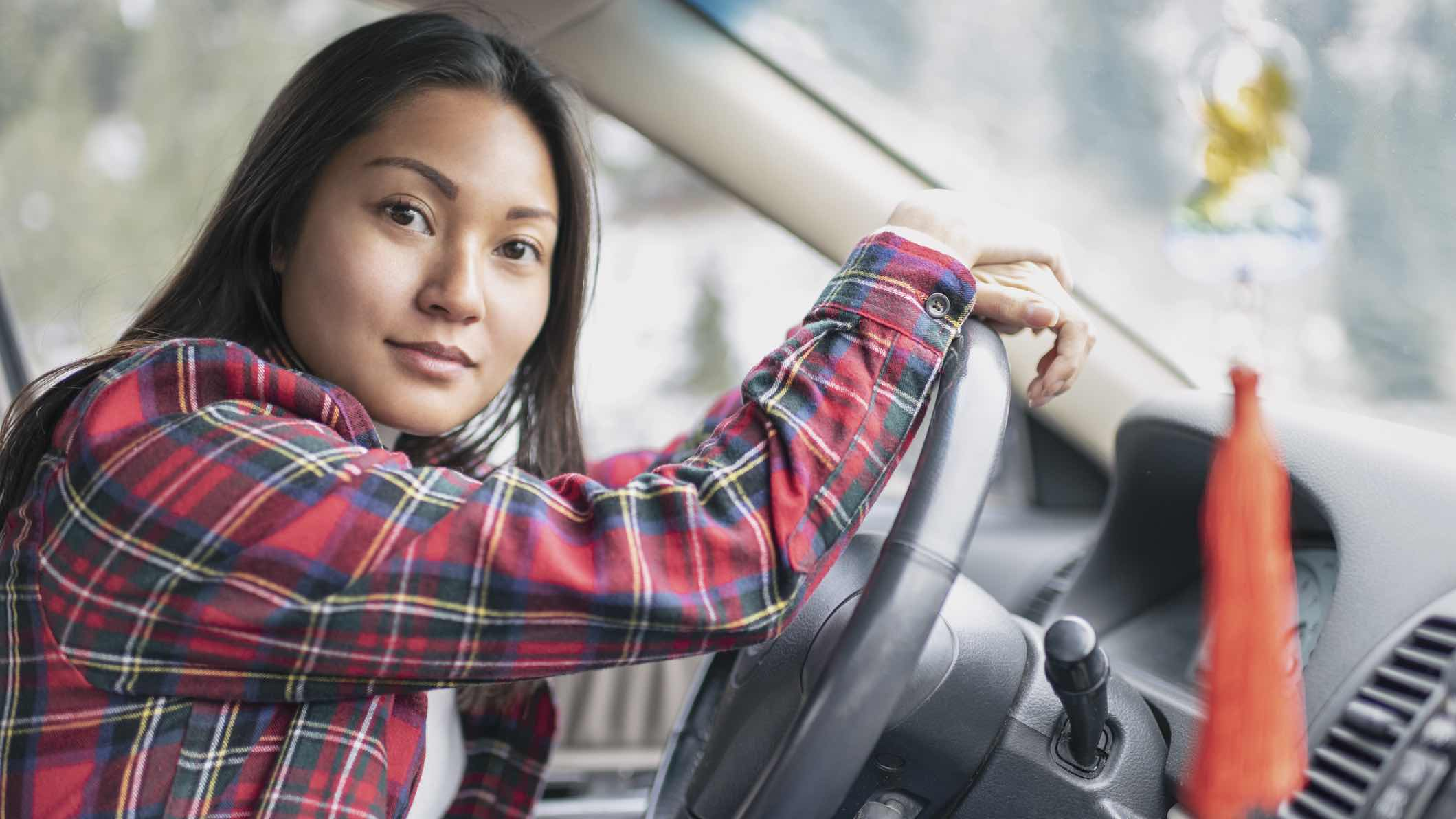 Young person sitting in drivers seat, considering car registration costs.