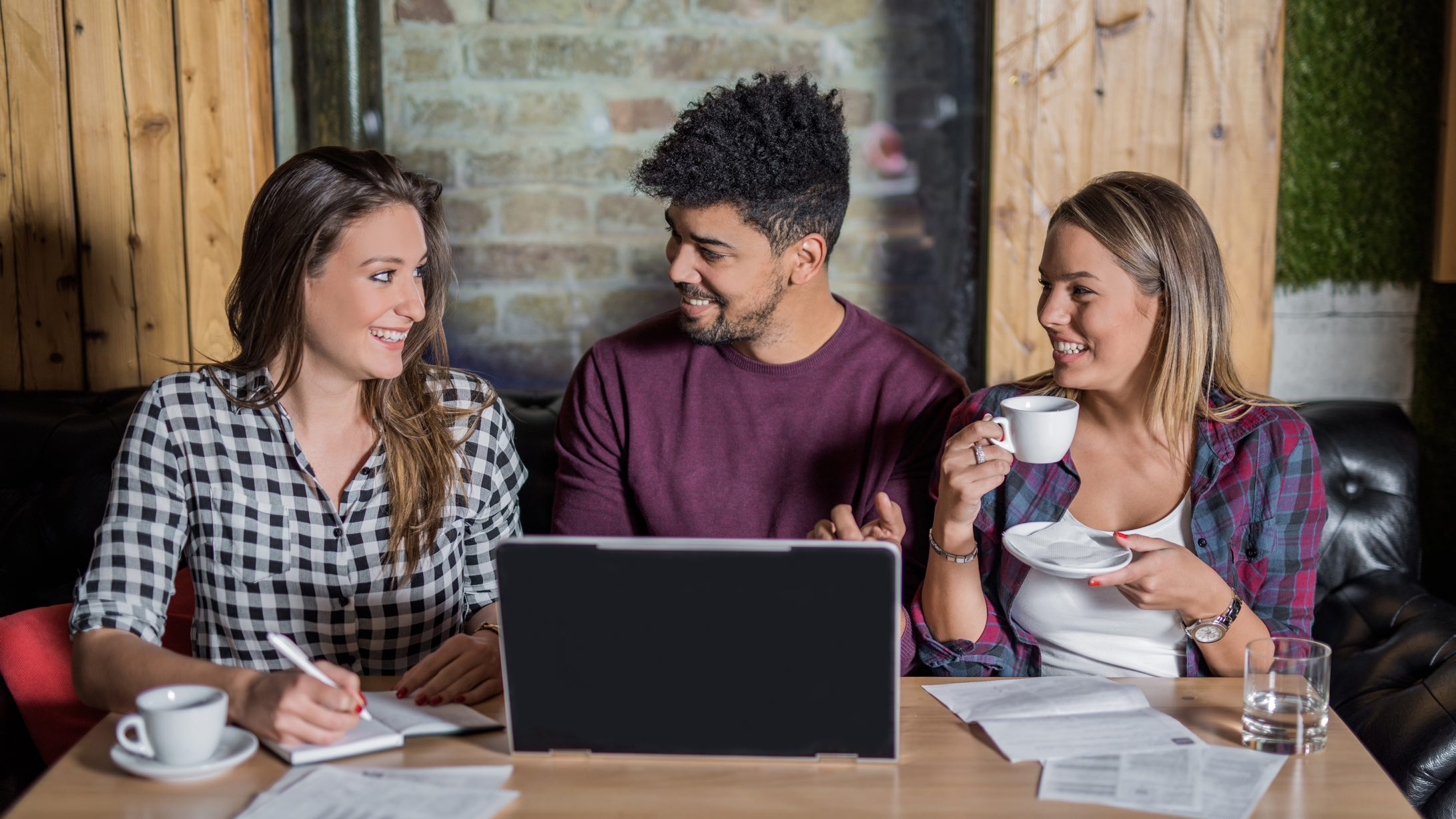 Three people sitting at a table drinking coffee, looking at paperwork and a laptop as they assess savings account interest rates.