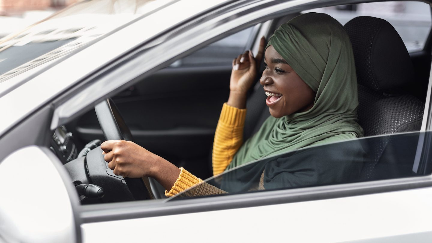 woman driving used car and smiling