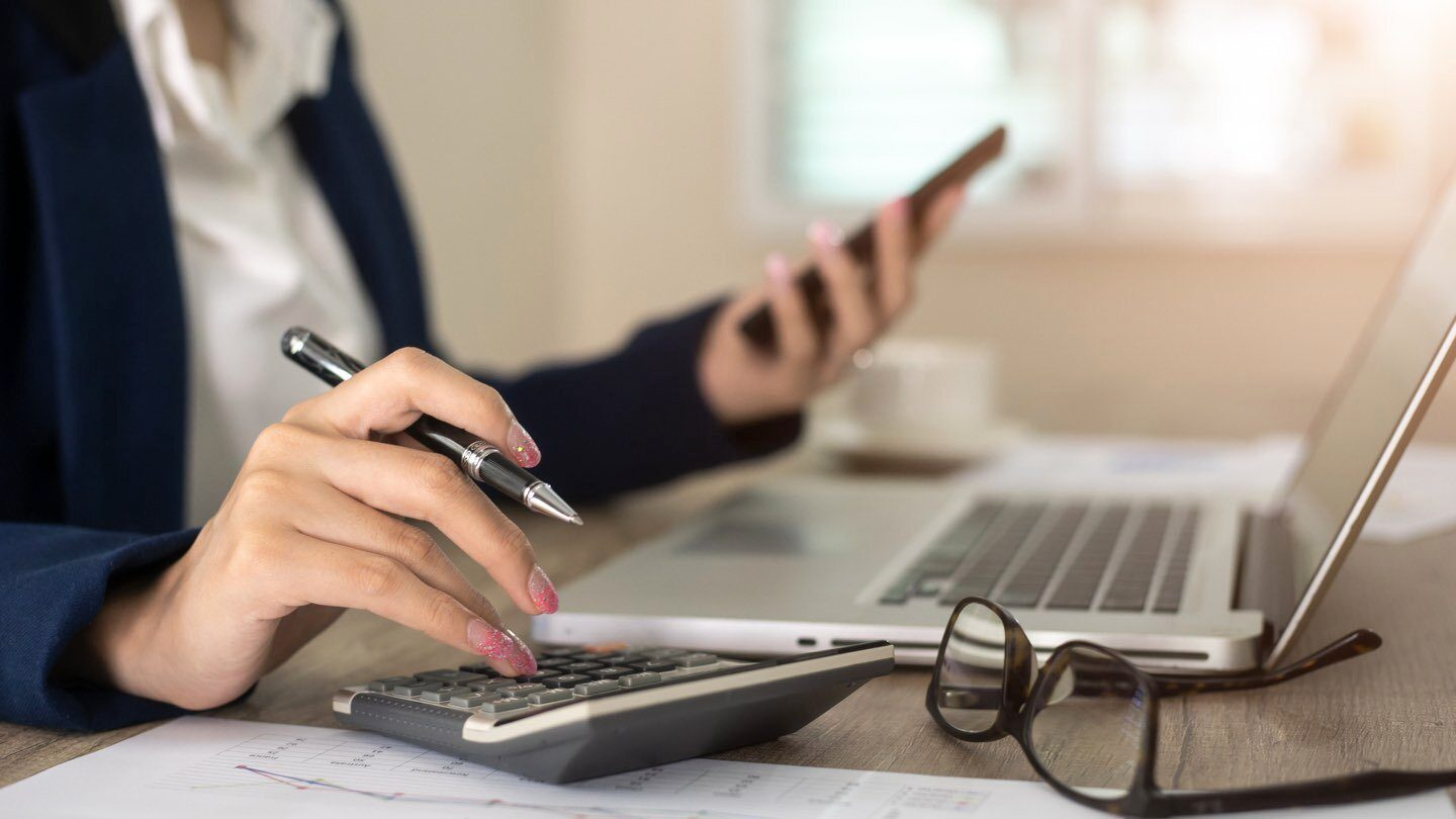 woman using a calculated to calculate how much she will save when she refinances her home loan
