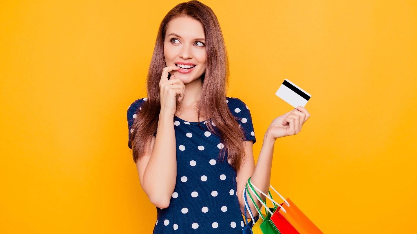 woman in front of yellow background playfully holds her Suncorp PayLater card and bags from shopping now and paying later