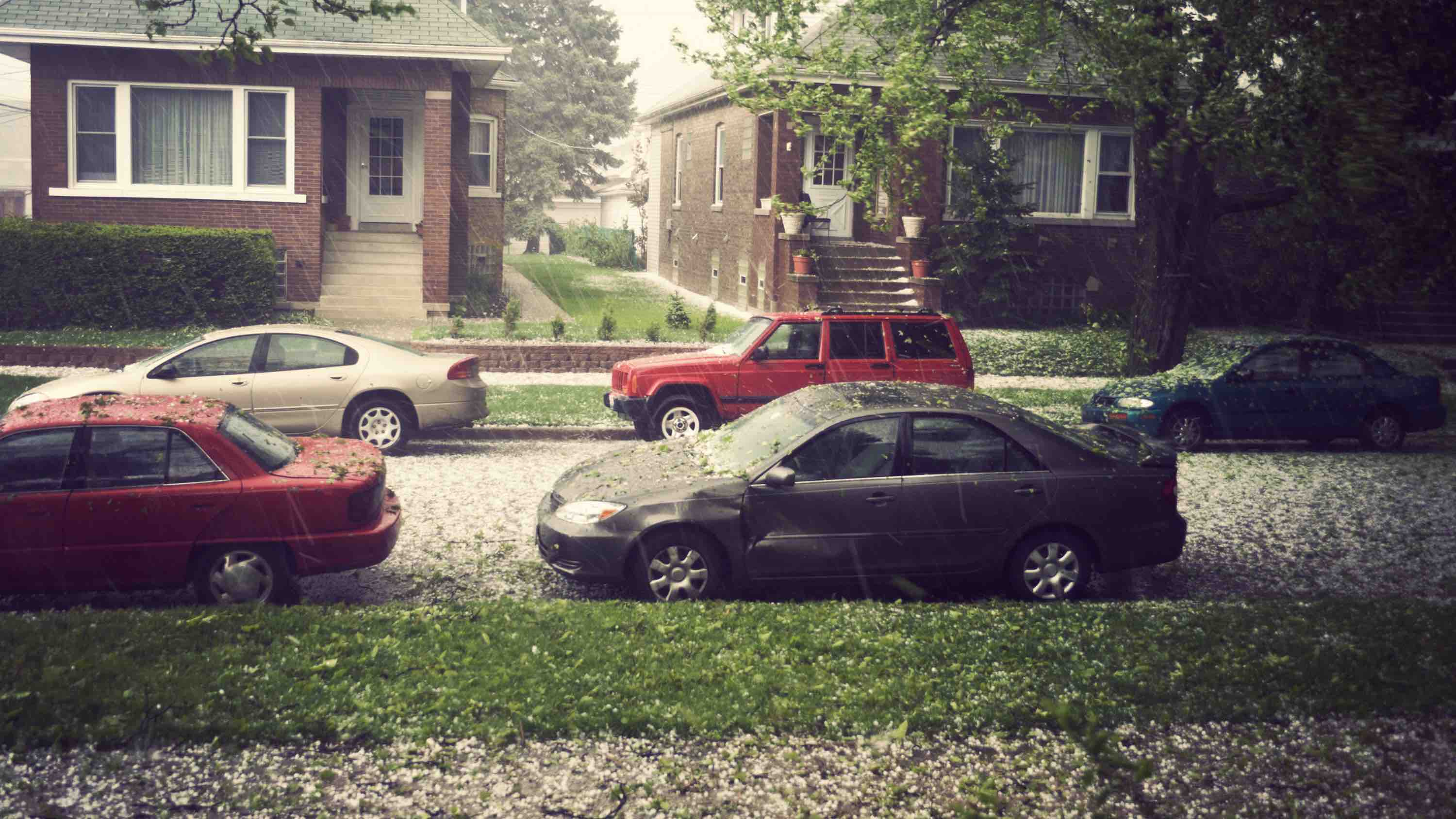 Houses and cars getting hit by hail and damaged during a storm.