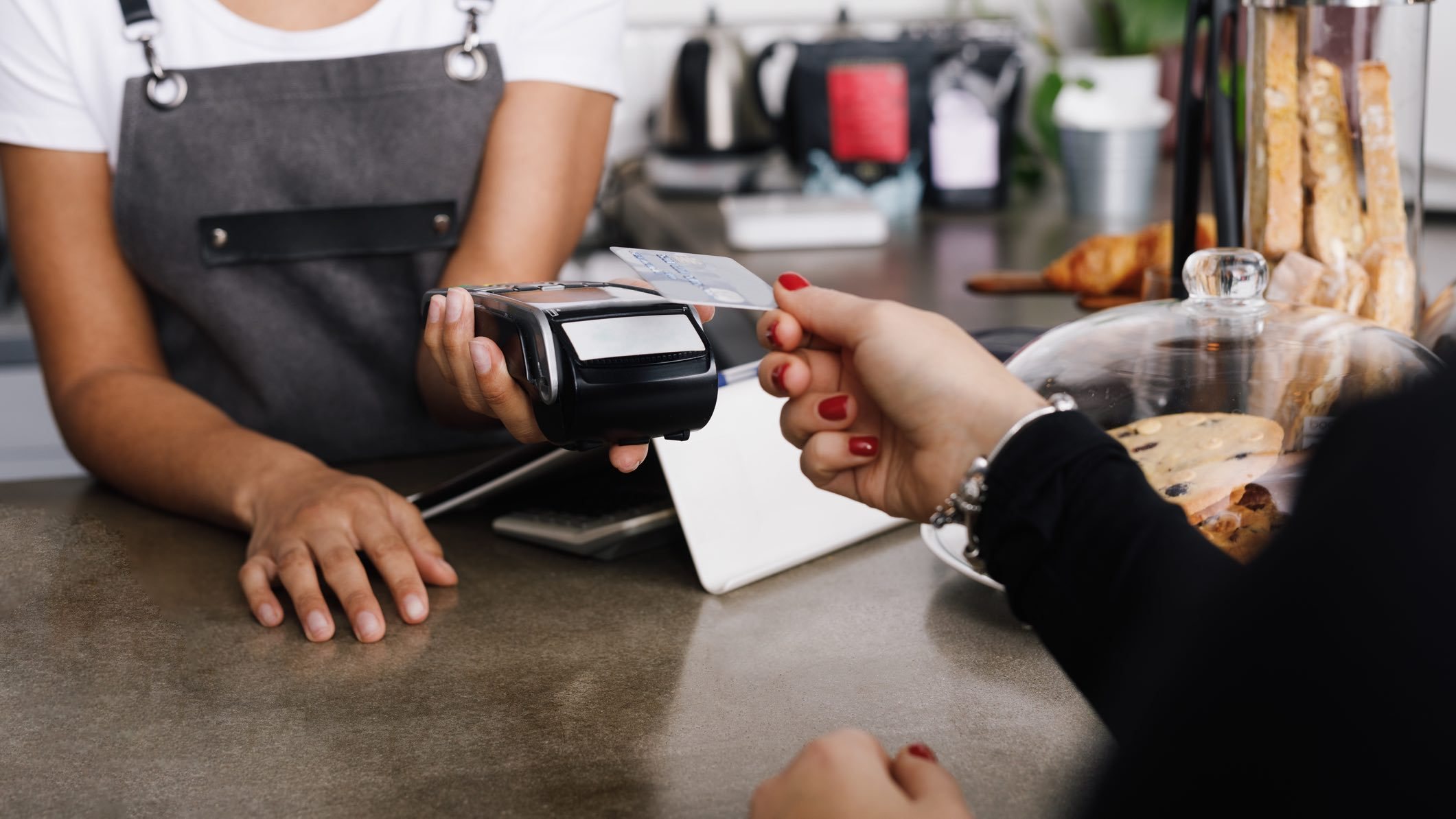 Person paying with card via EFTPOS machine at a cafe.