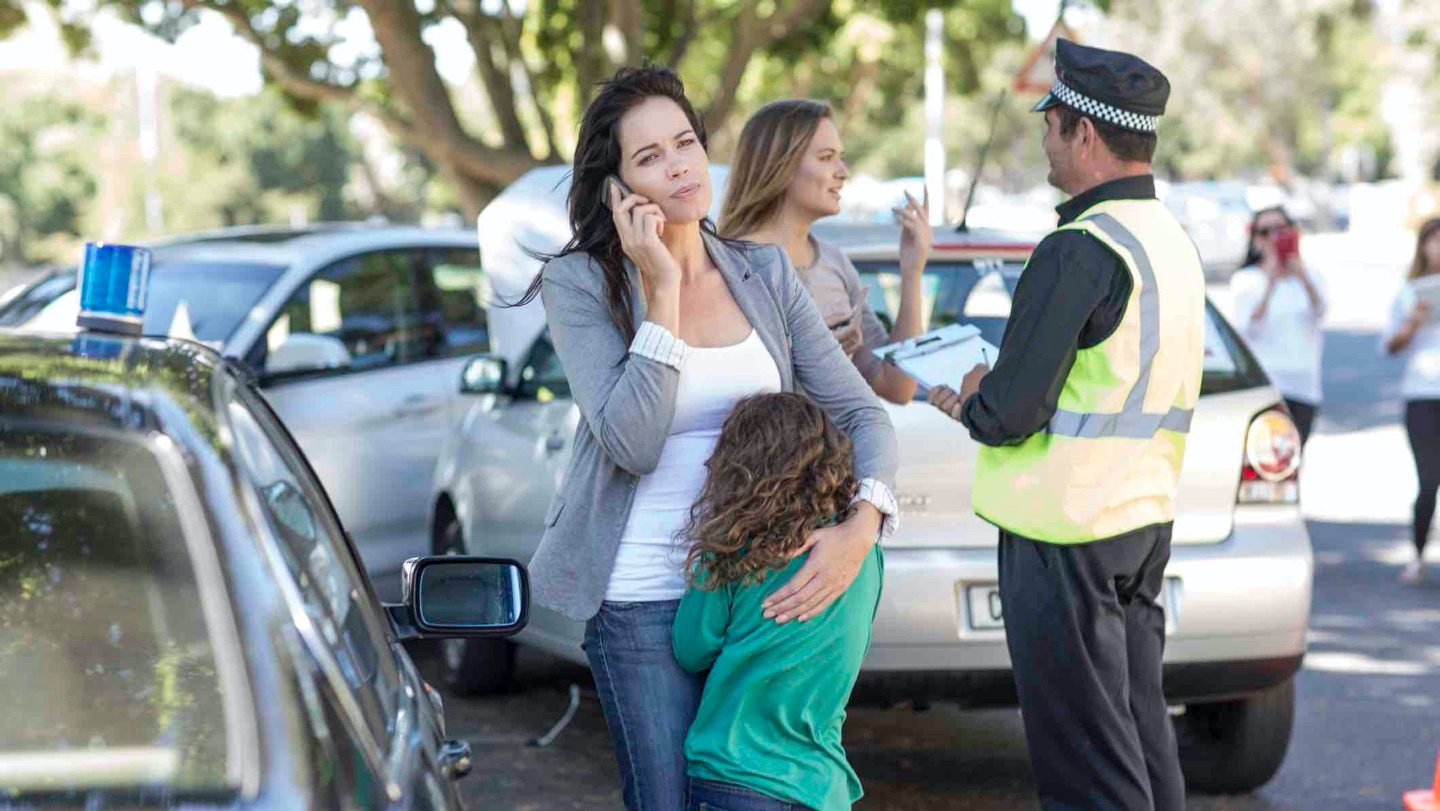 A woman talks on mobile phone, while comforting child after a car accident.