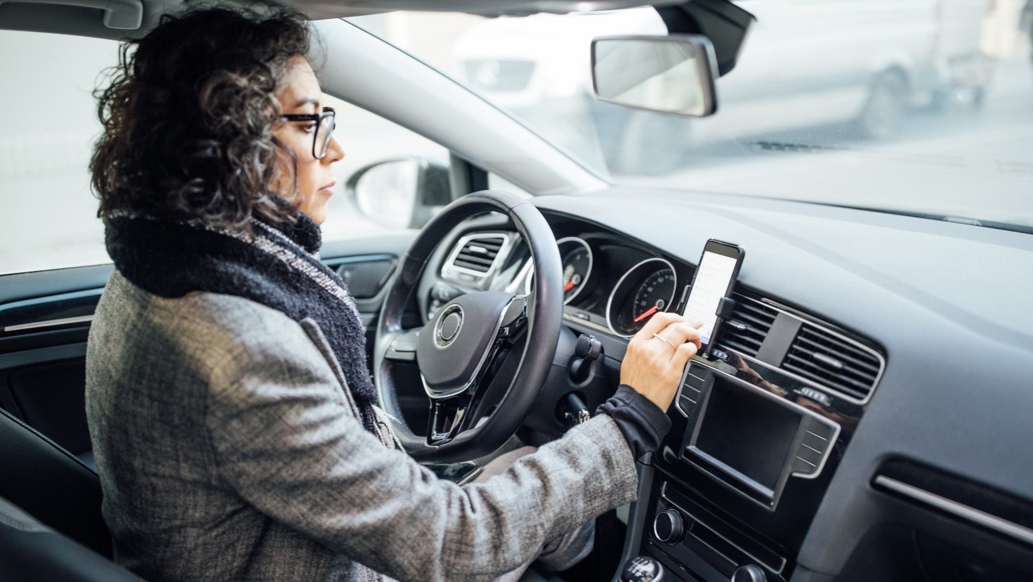 Woman sitting in car in drivers seat, using phone and insurtech devices.