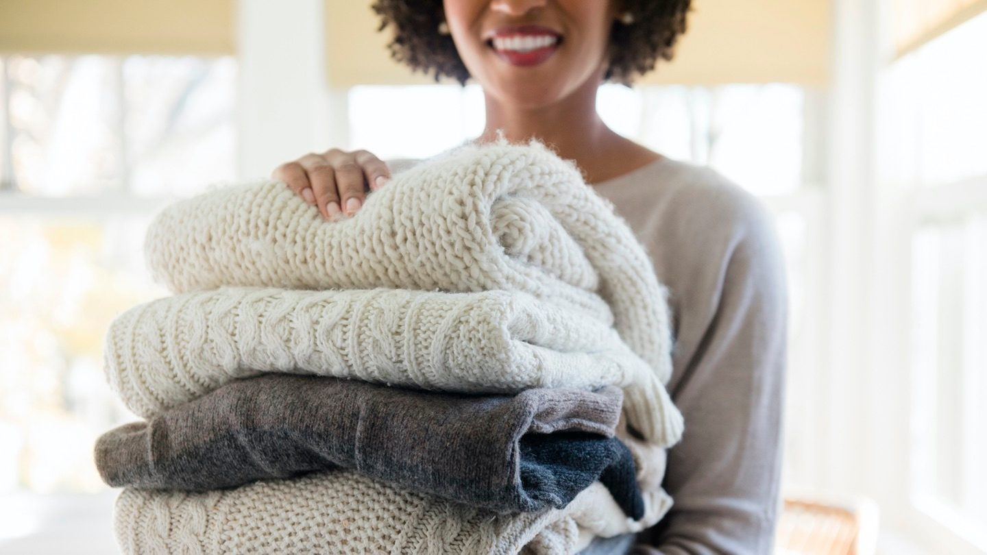 Woman holds stack of knitted jumpers.