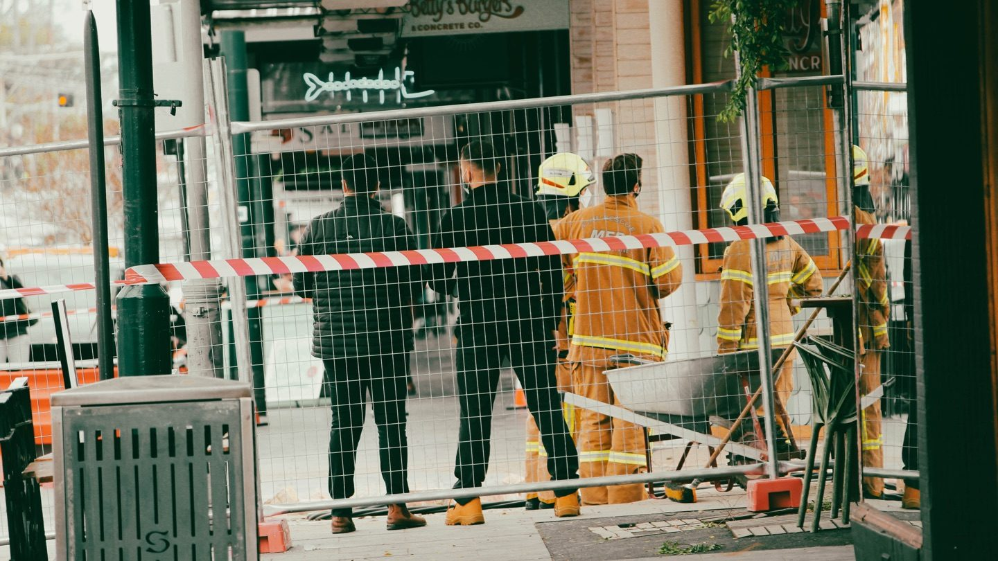 Emergency workers stand on Melbourne street after earthquake.