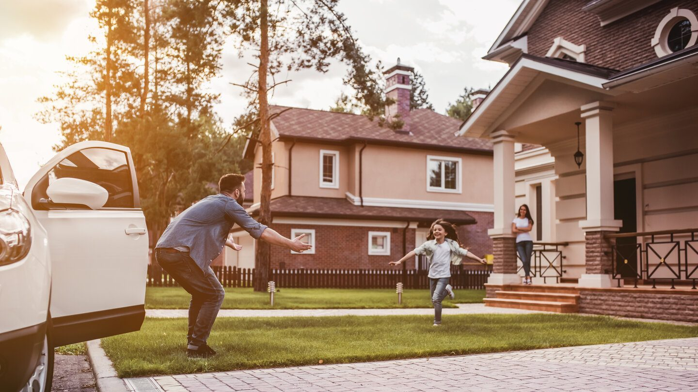 Child running to their dad across the lawn as mum watched from the house's patio