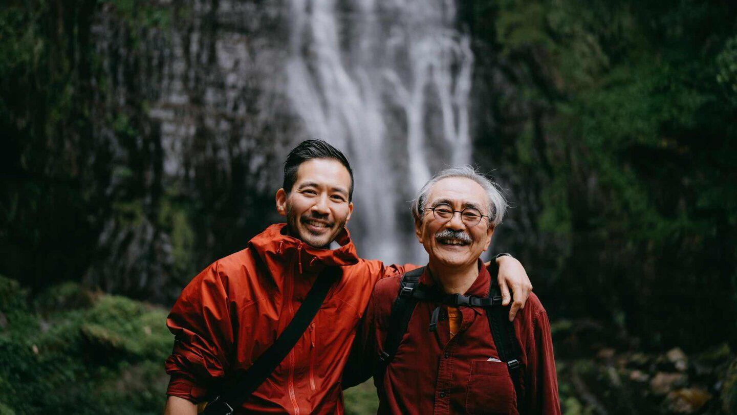 Father and son in front of a waterfall smiling together