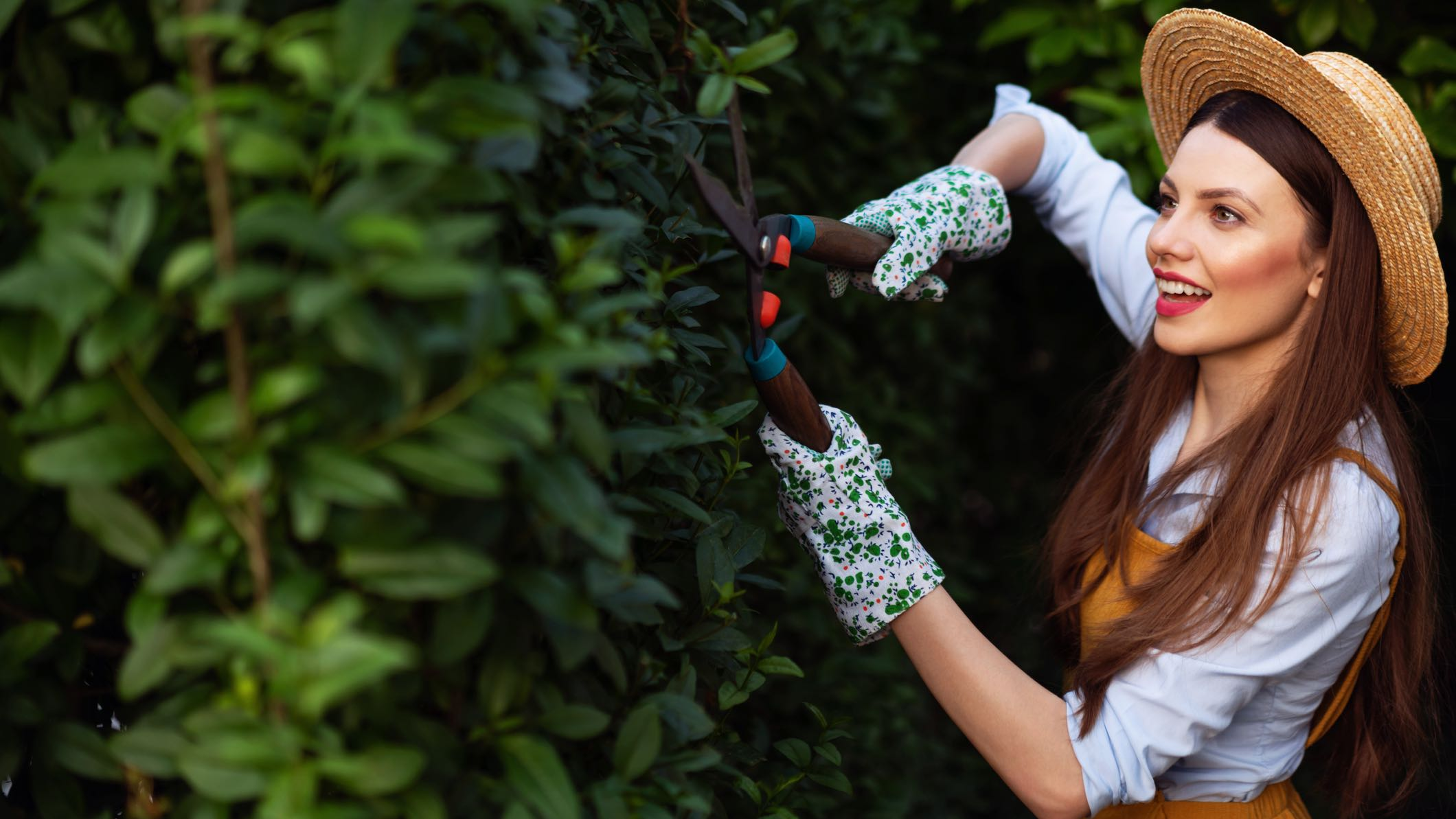 Woman in hat cutting hedge as home loan interest rates drop.