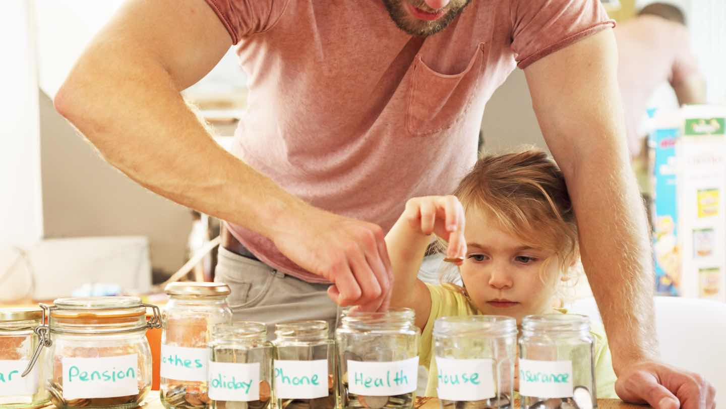 Father and daughter put savings in jars.
